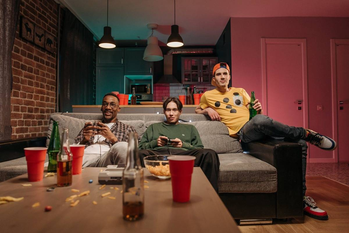 three male friends sitting on couch in messy room