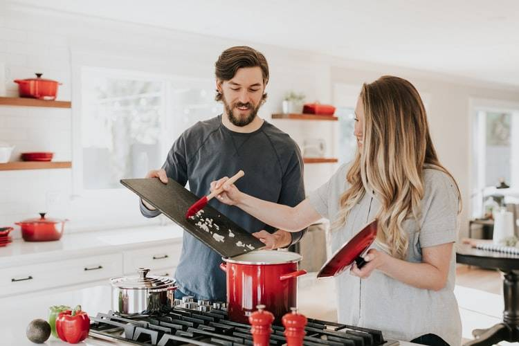 man and woman cooking together in a home kitchen