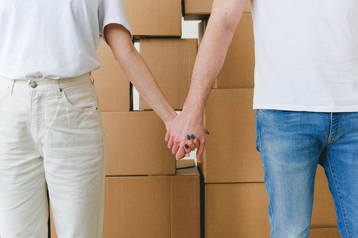 couple holding hands standing in front of brown boxes