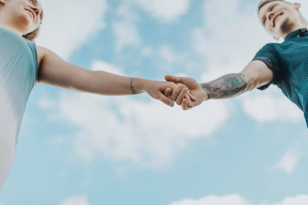 couple holds hands in bright sky
