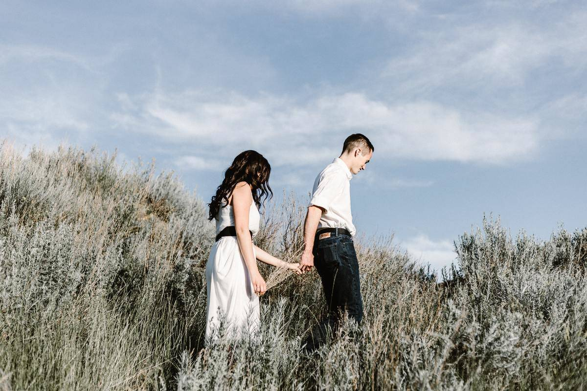 couple holds hands walking in a field