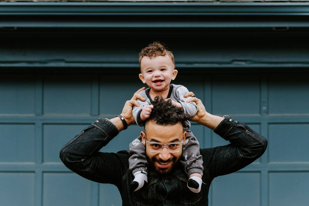 dad holding up kid on his shoulders in front of garage