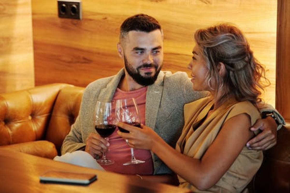 two people cheersing wine glasses on a date