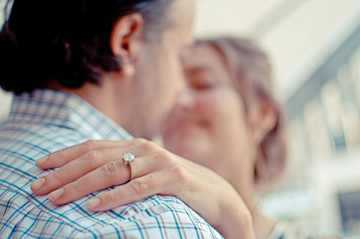 woman wearing engagement ring in focus while hugging man