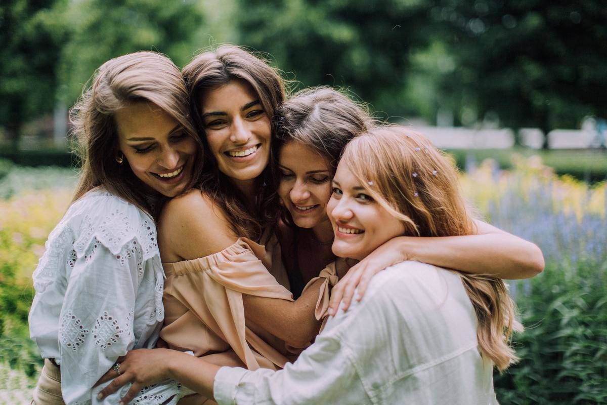 group of women hugging in a park