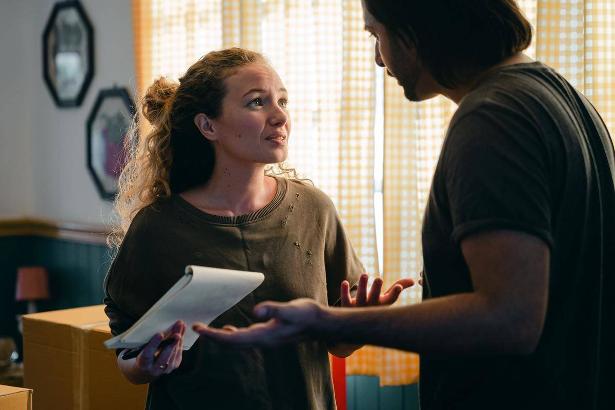 Woman holding notebook looking at man, mid-argument