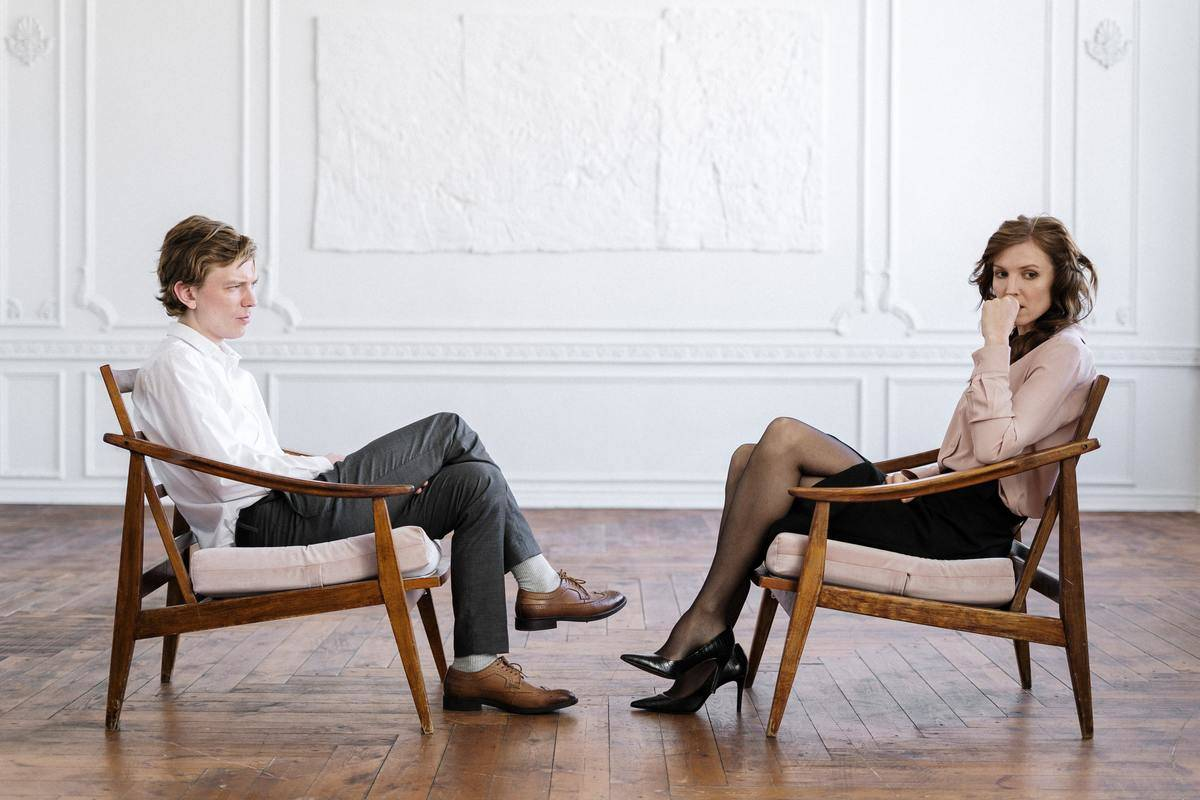 man and woman sit across each other at therapy