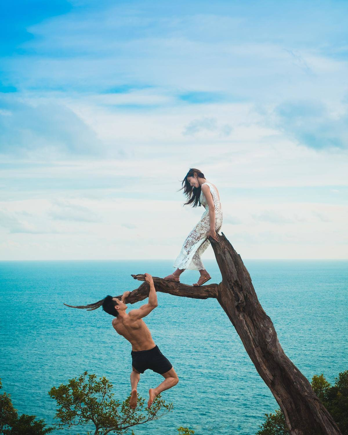 man climbing tree by the sea to reach woman sitting on top