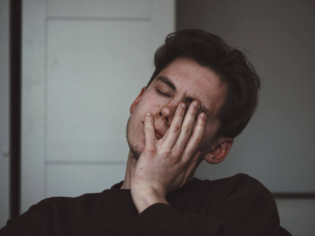 man looking upset and putting his hand to his face