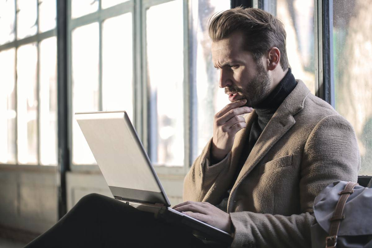 man looking at laptop with serious face