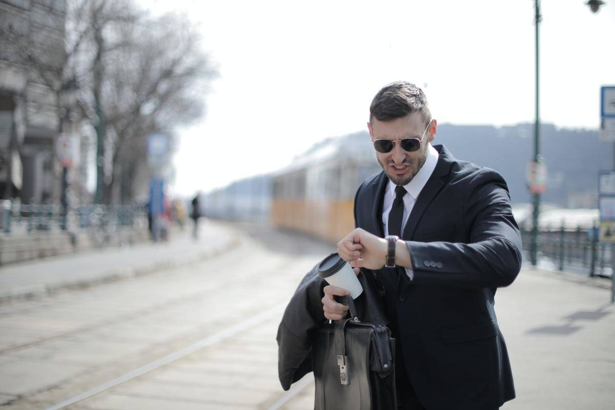 Man in a suit and sunglasses outside checking his watch