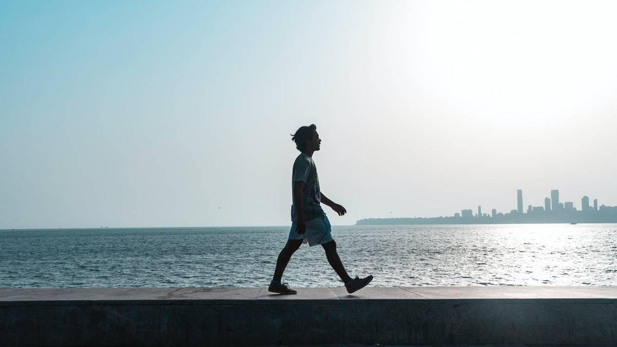 man strolling beside water