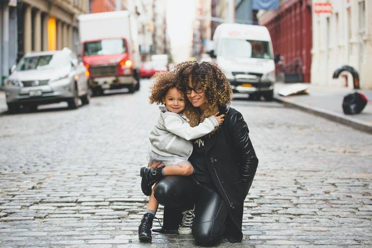 mother and young daughter on street