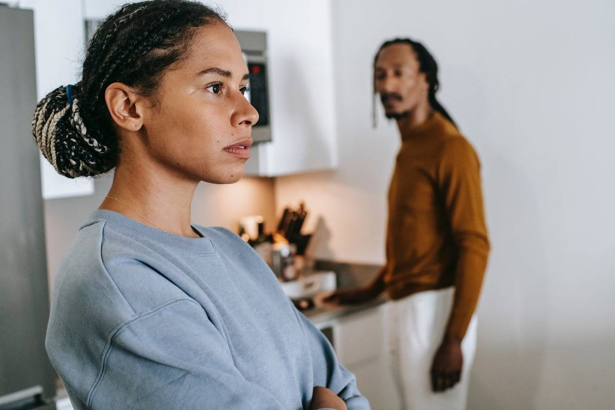 woman staring off into distance as man stares at her in kitchen