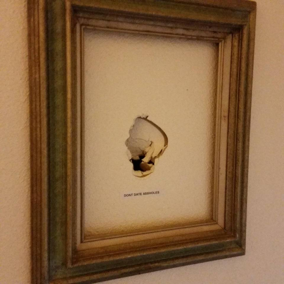Hole in wall with a picture frame around it