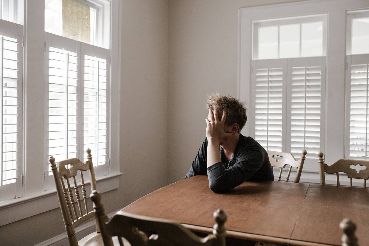 man sitting at kitchen table with his head in his hands