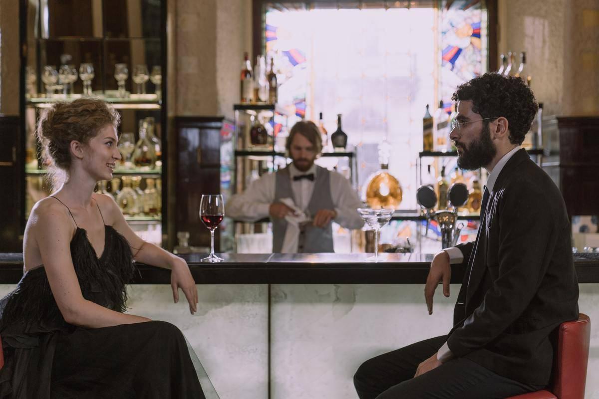man and woman sit at bar chatting