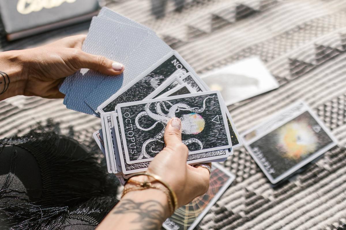 woman looking through tarot cards on blanket