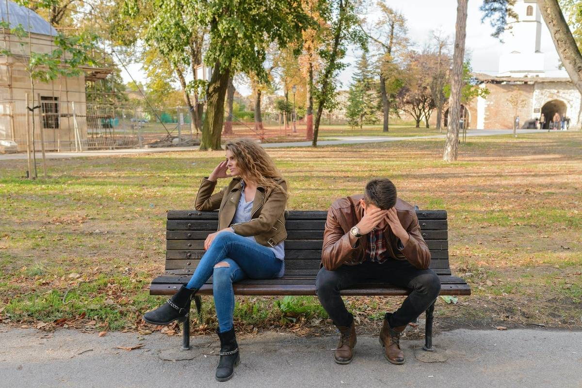 man and woman sitting on park bench looking distressed