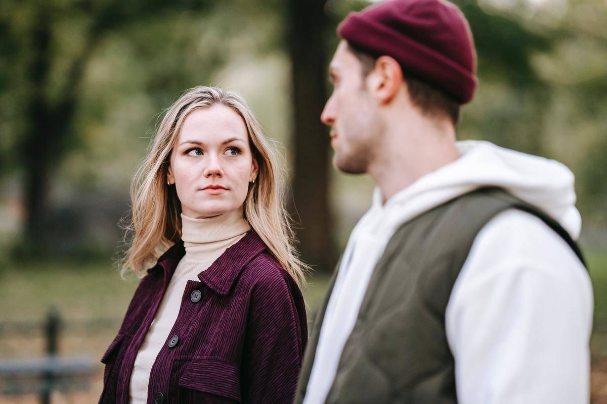 woman and man walking in park looking at each other