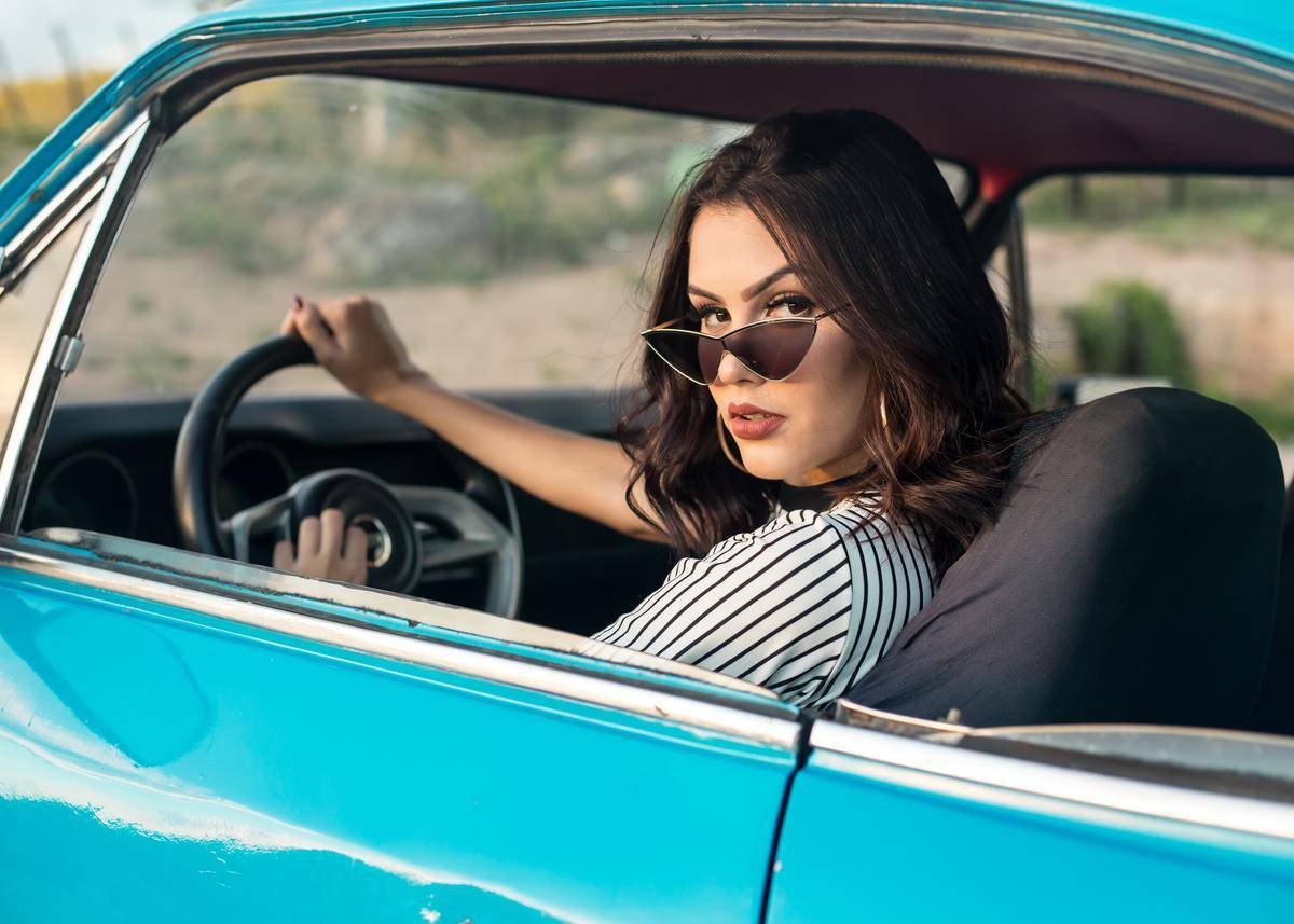 woman driving blue car and posing for camera