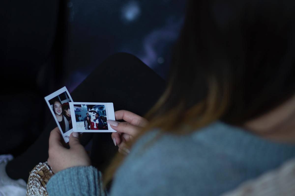 woman holding polaroids in the dark