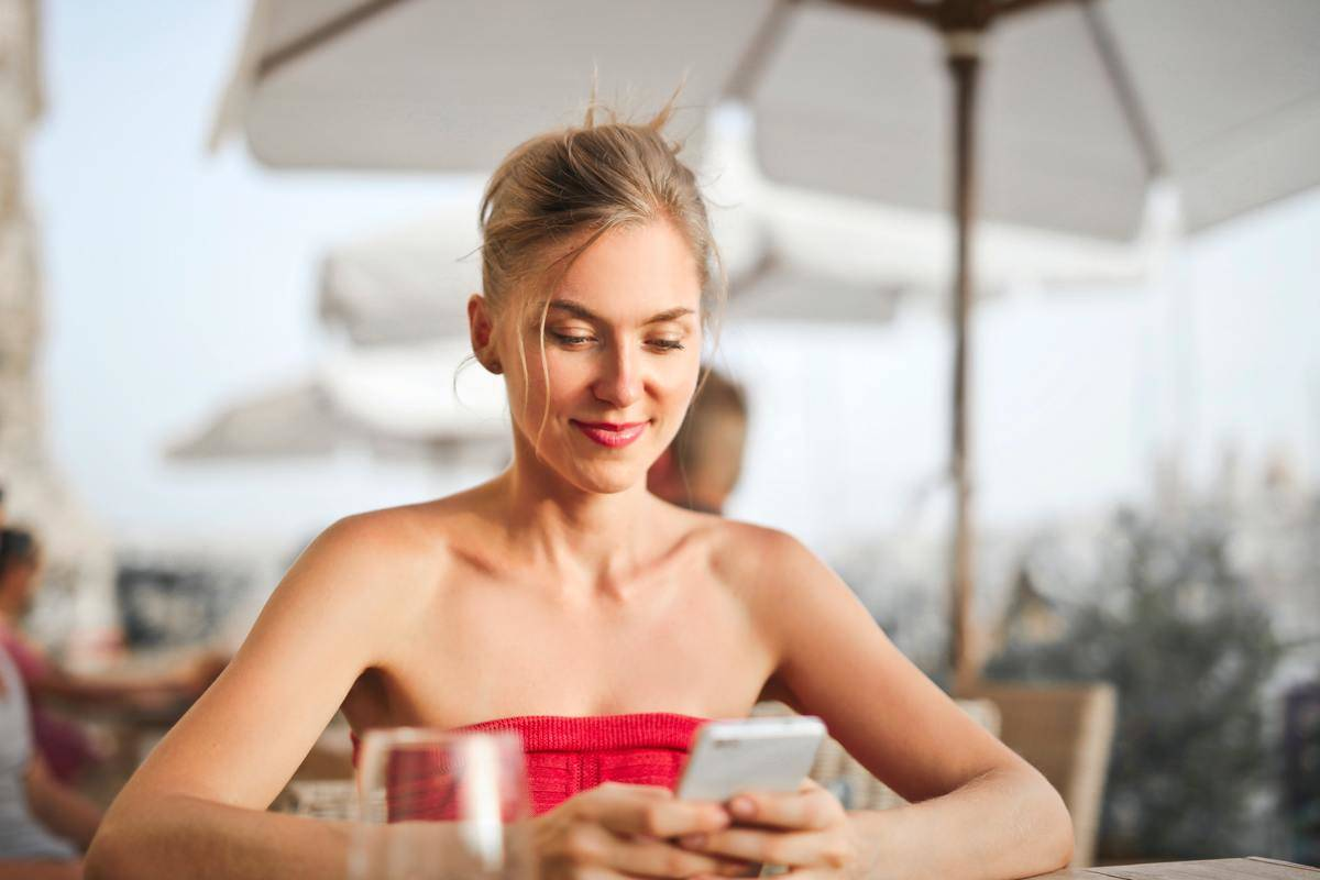 woman looking down at phone at restaurant