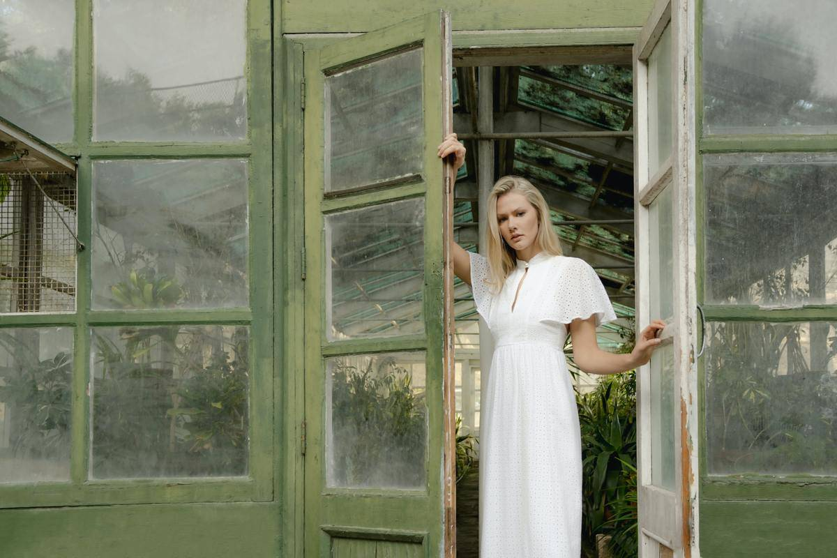 woman standing at door in white dress