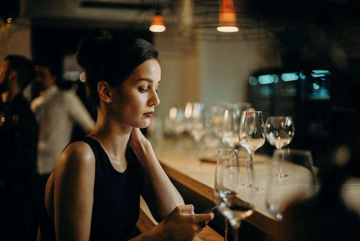 woman texting at the bar