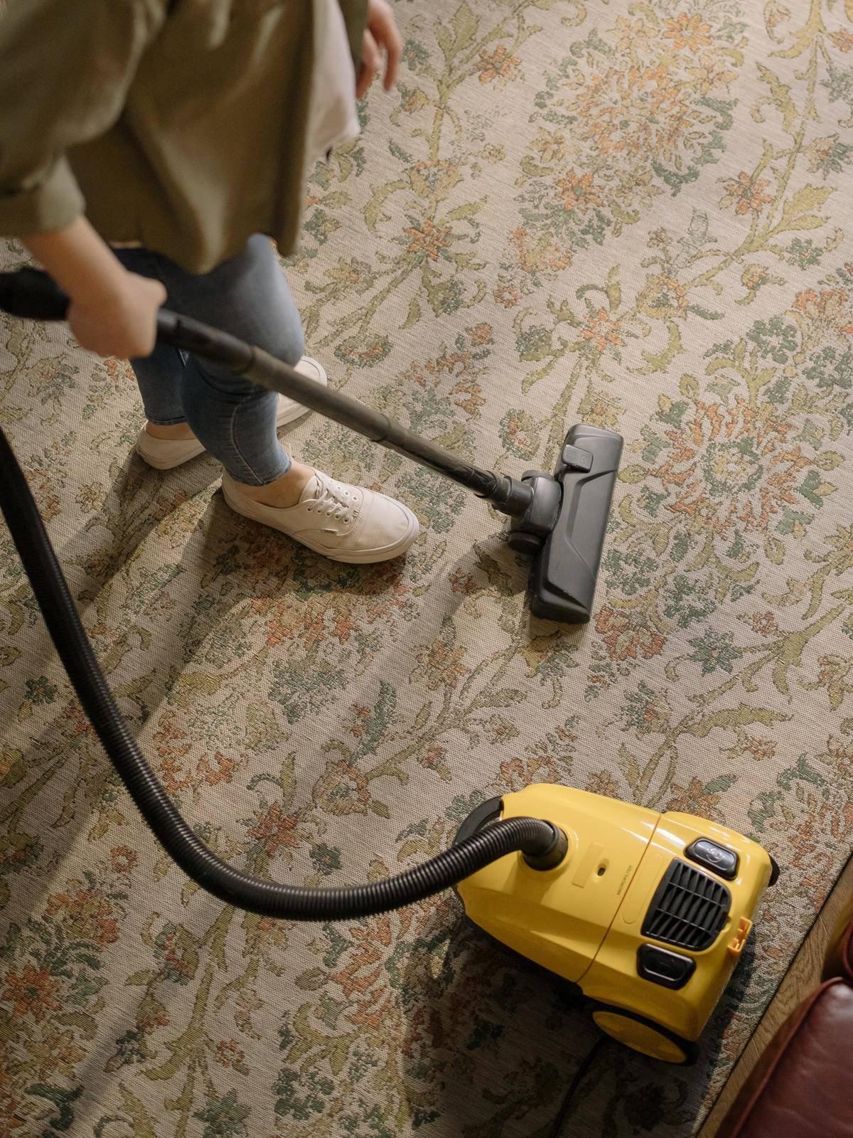 woman vacuuming the carpet
