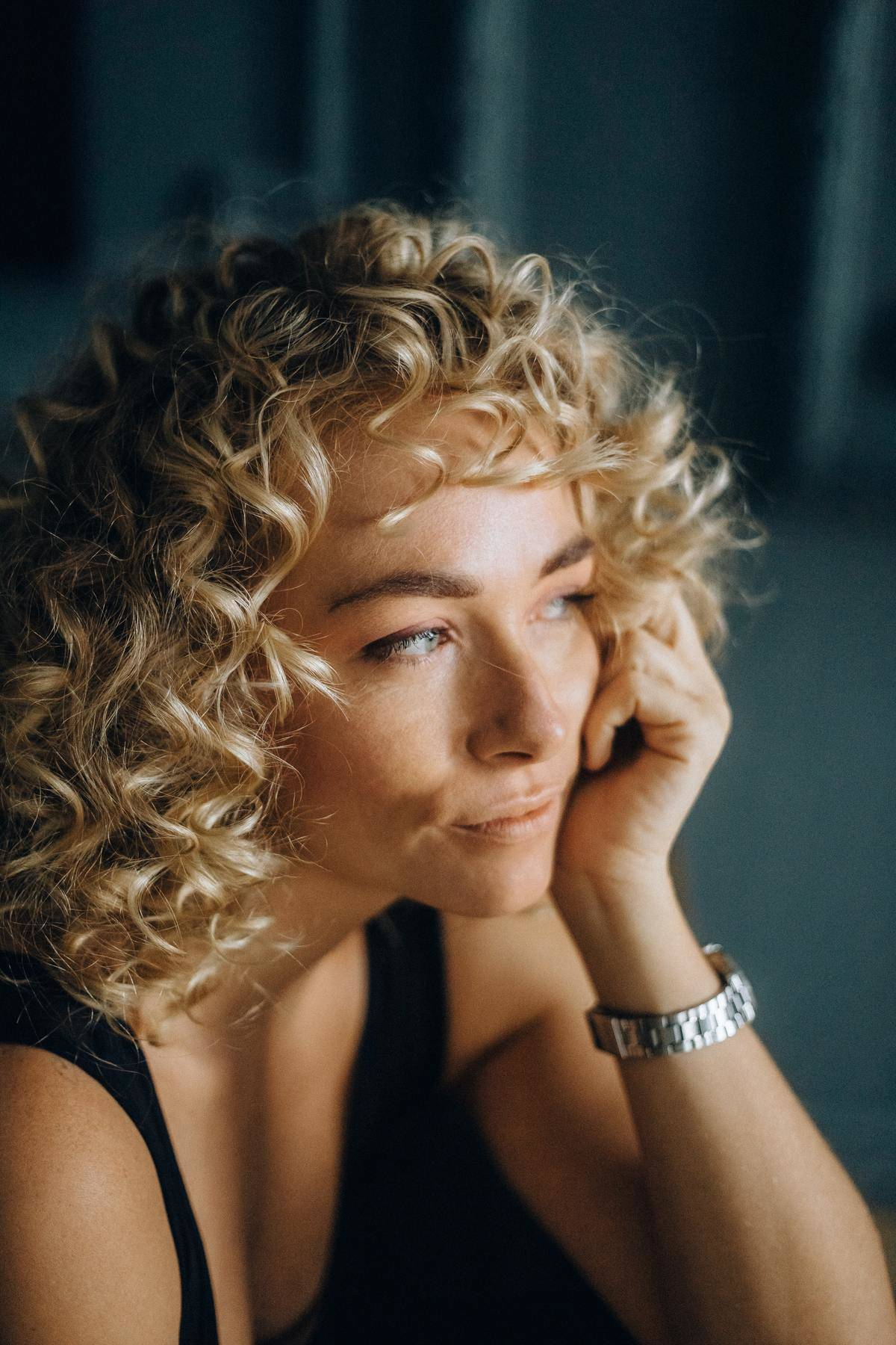 woman with curly hair and hand on her cheek