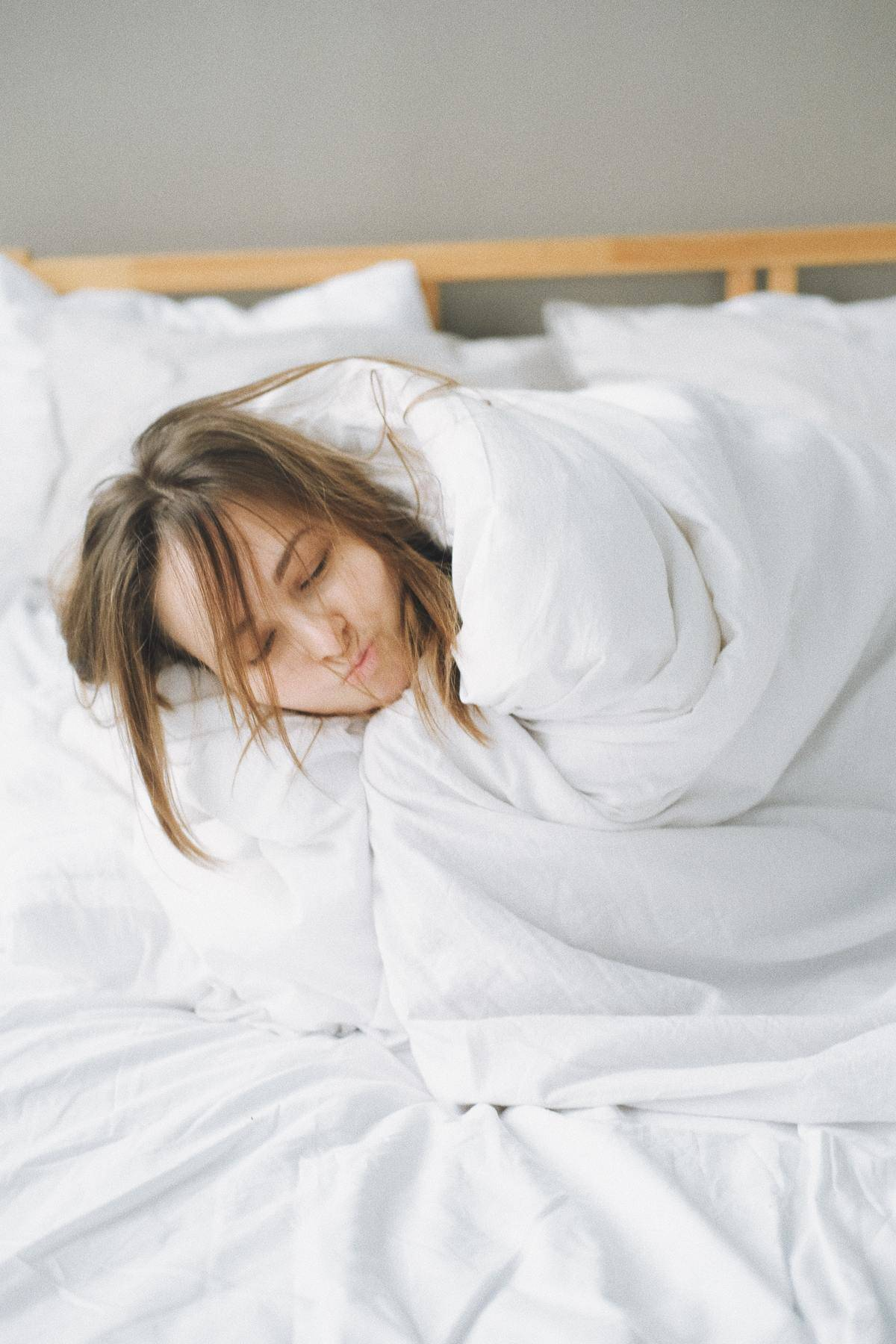 woman wrapped in white duvet