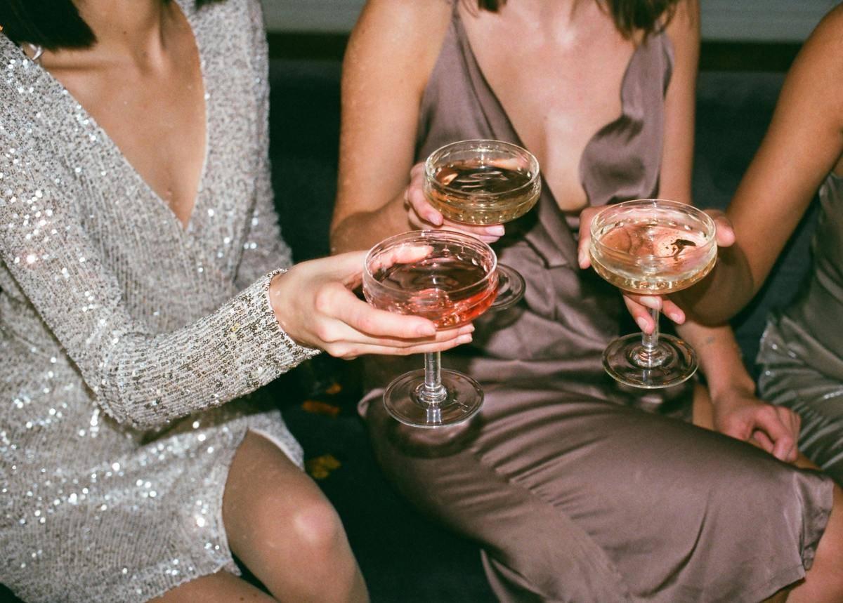 women in fancy dresses cheers cocktails