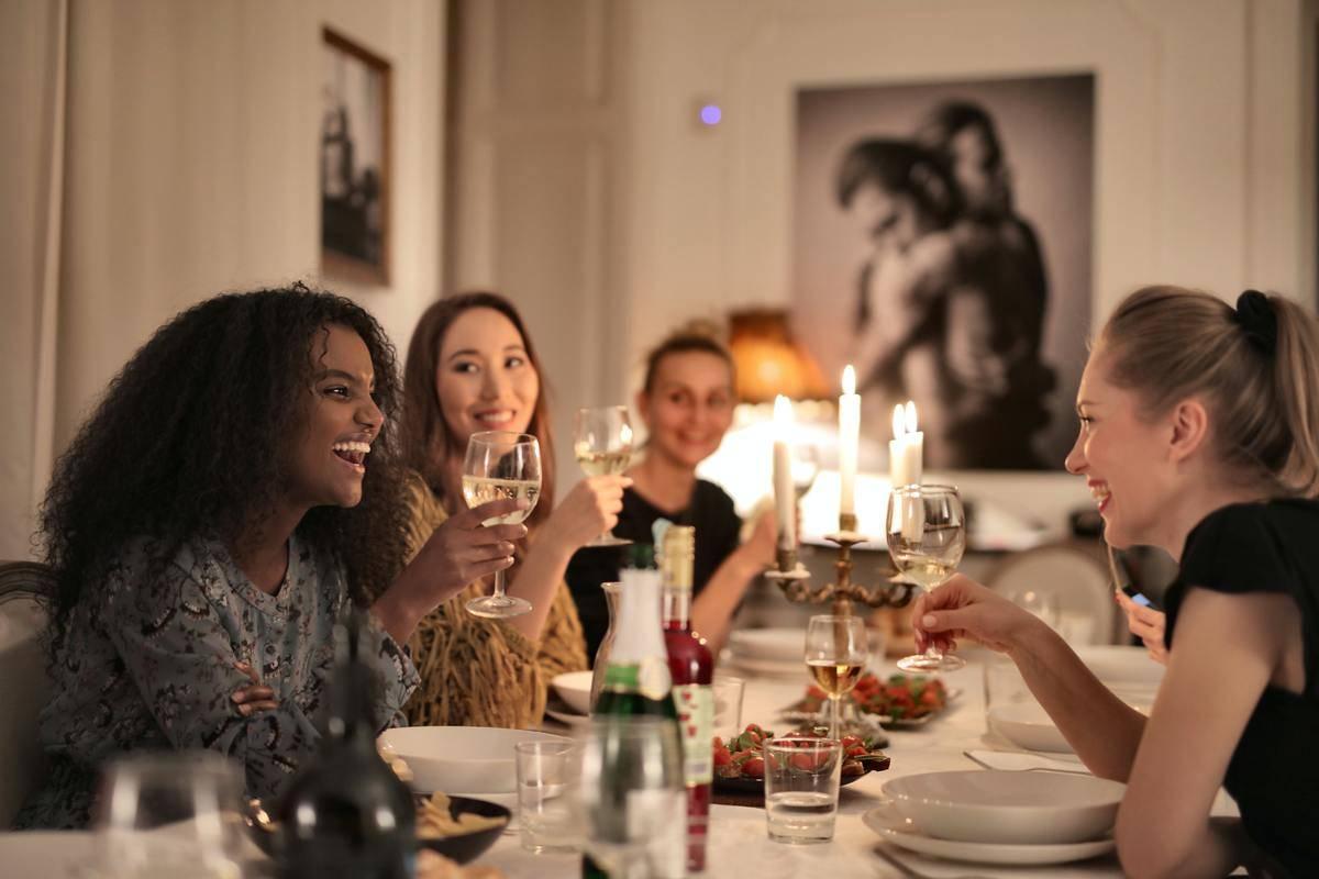 women having wine around dinner table