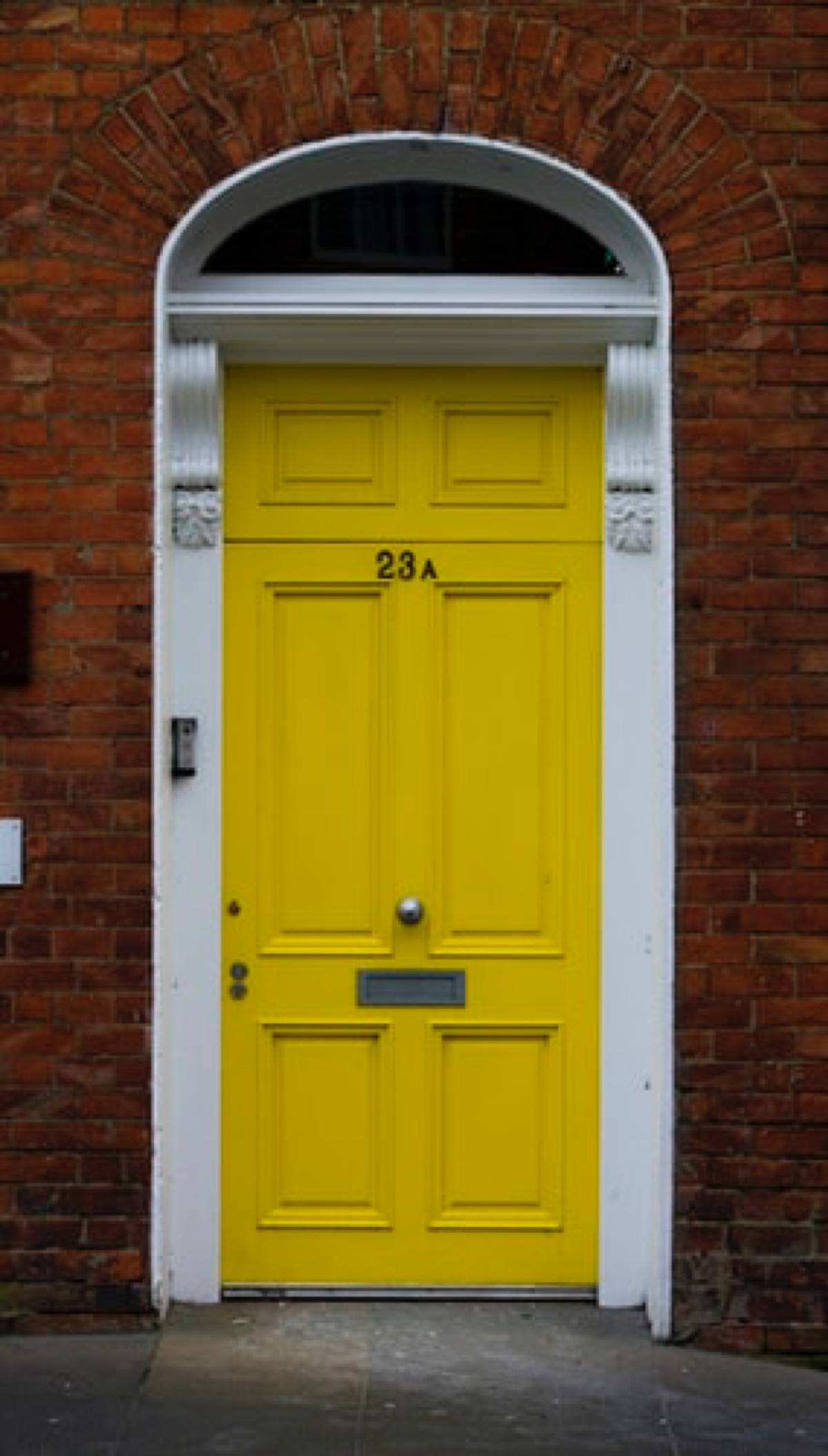 yellow front door against red brick wall