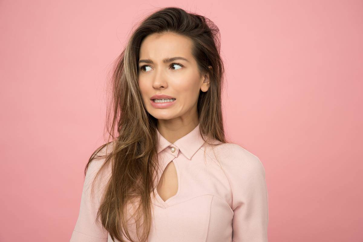 Woman standing against pink background making a cringe face
