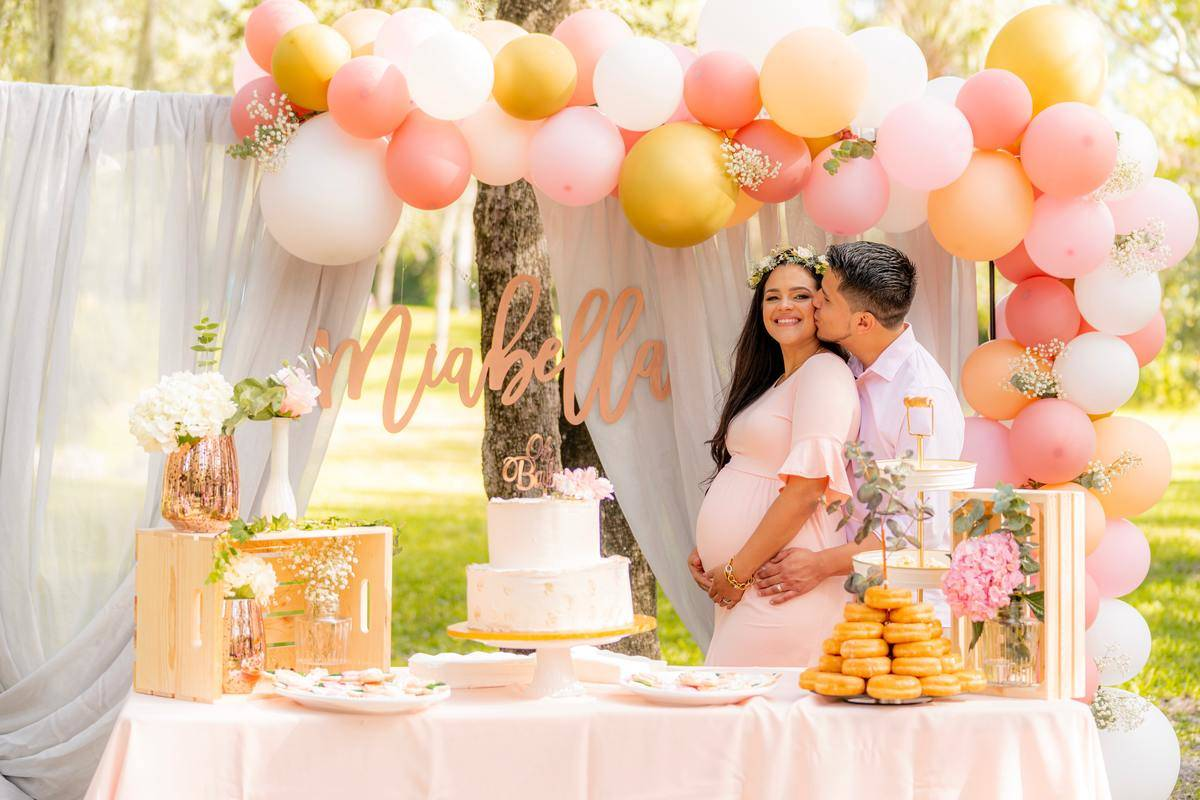 Husband hugs and kisses his pregnant wife while they attend her baby shower