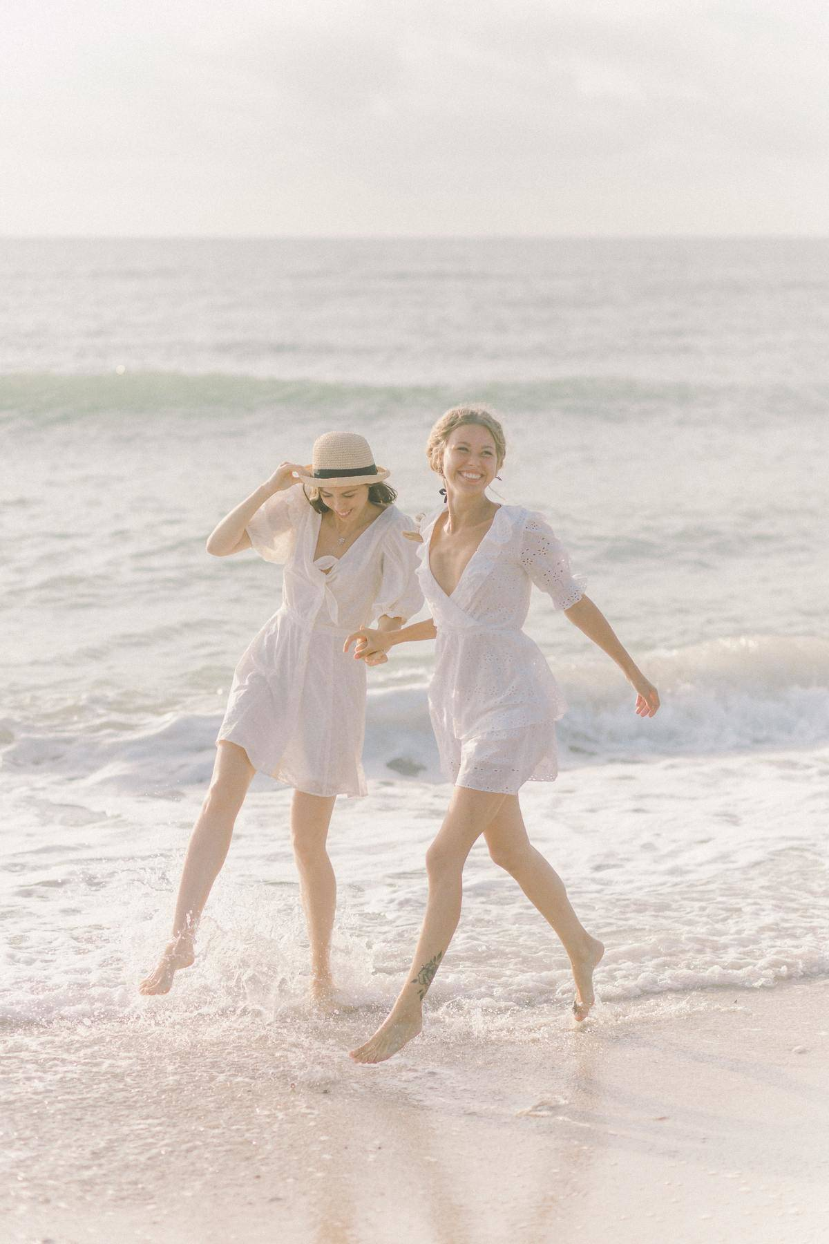 Two women in white dresses walk down the beach and hold hands