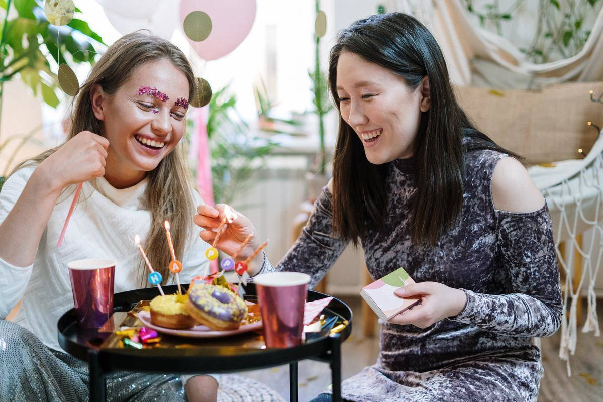 Two women laugh and smile at coffee table over birthday donuts