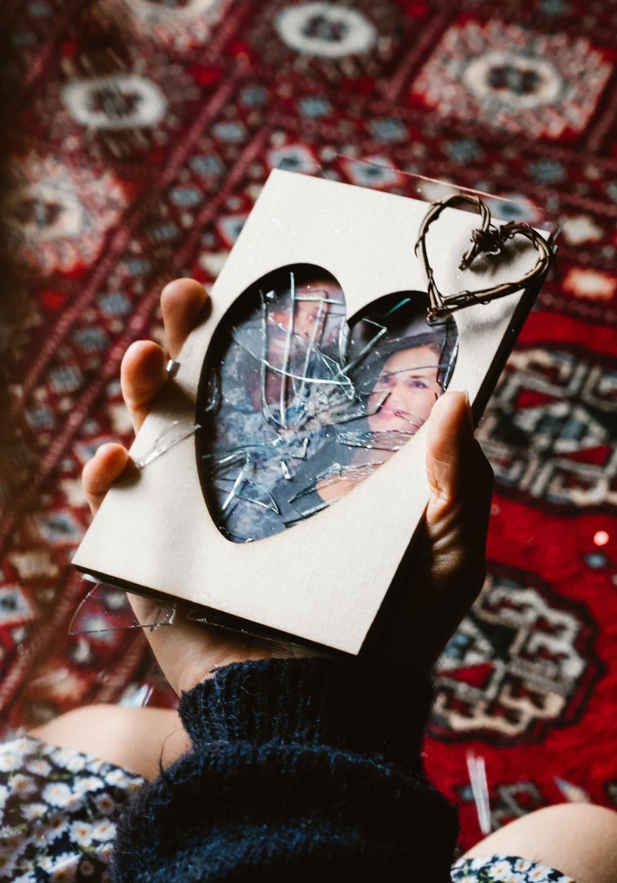 Broken frame photo in heart shape, smashed glass