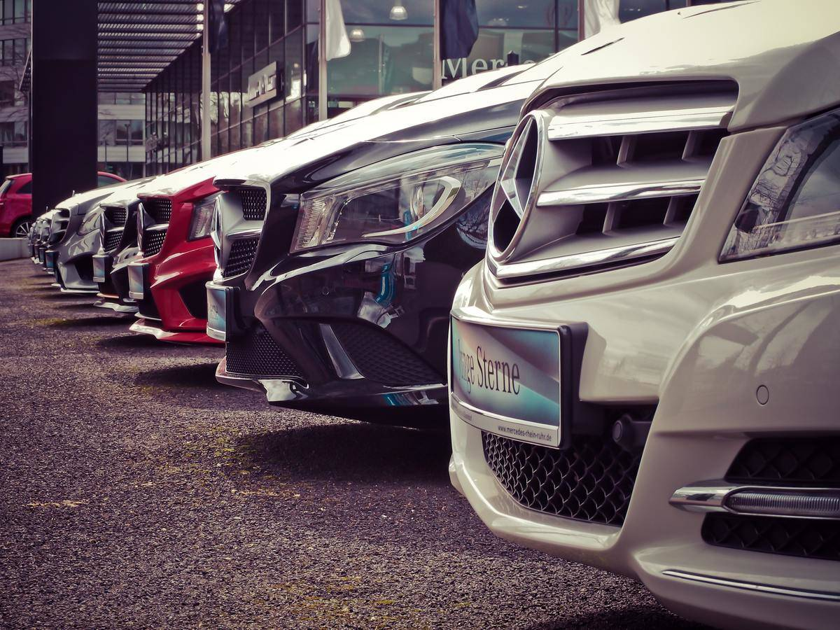 Row of white, red, and black vehicles at a car dealership