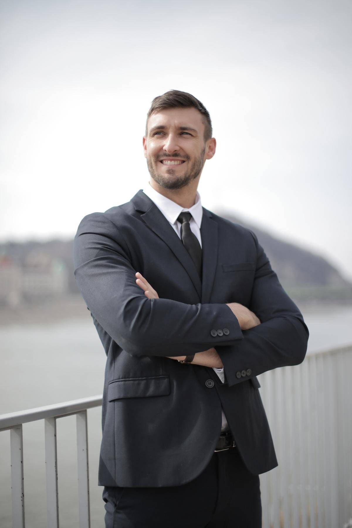 Confident man in a dark grey suit smiles while he crosses his arms