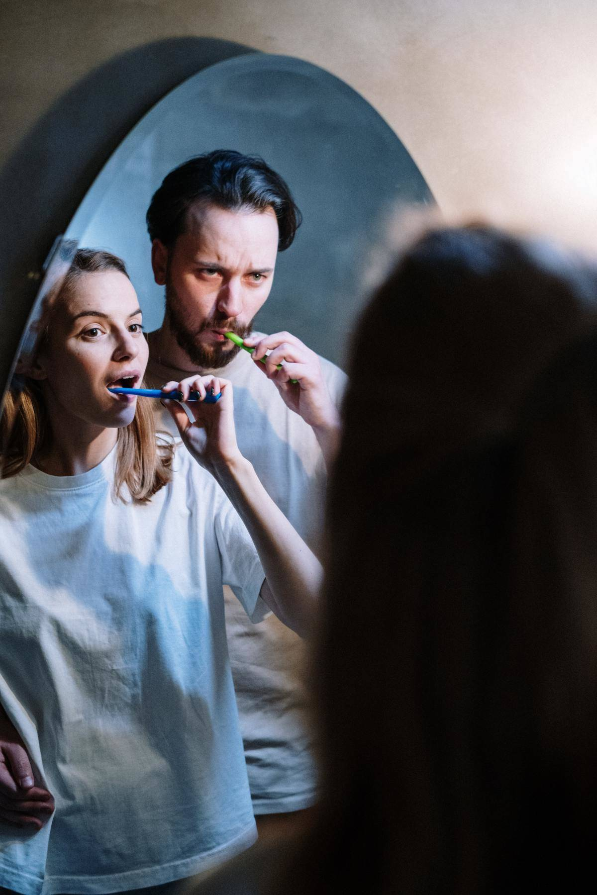 Couple stands in front of mirror brushing teeth