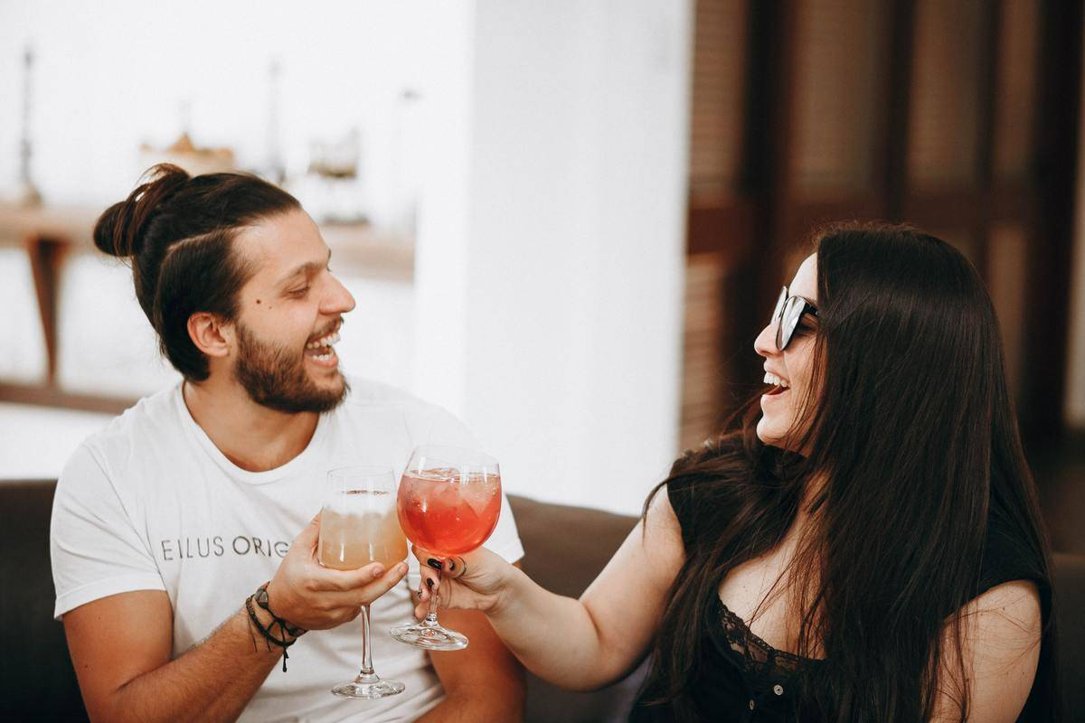 Two people cheers drinks on couch
