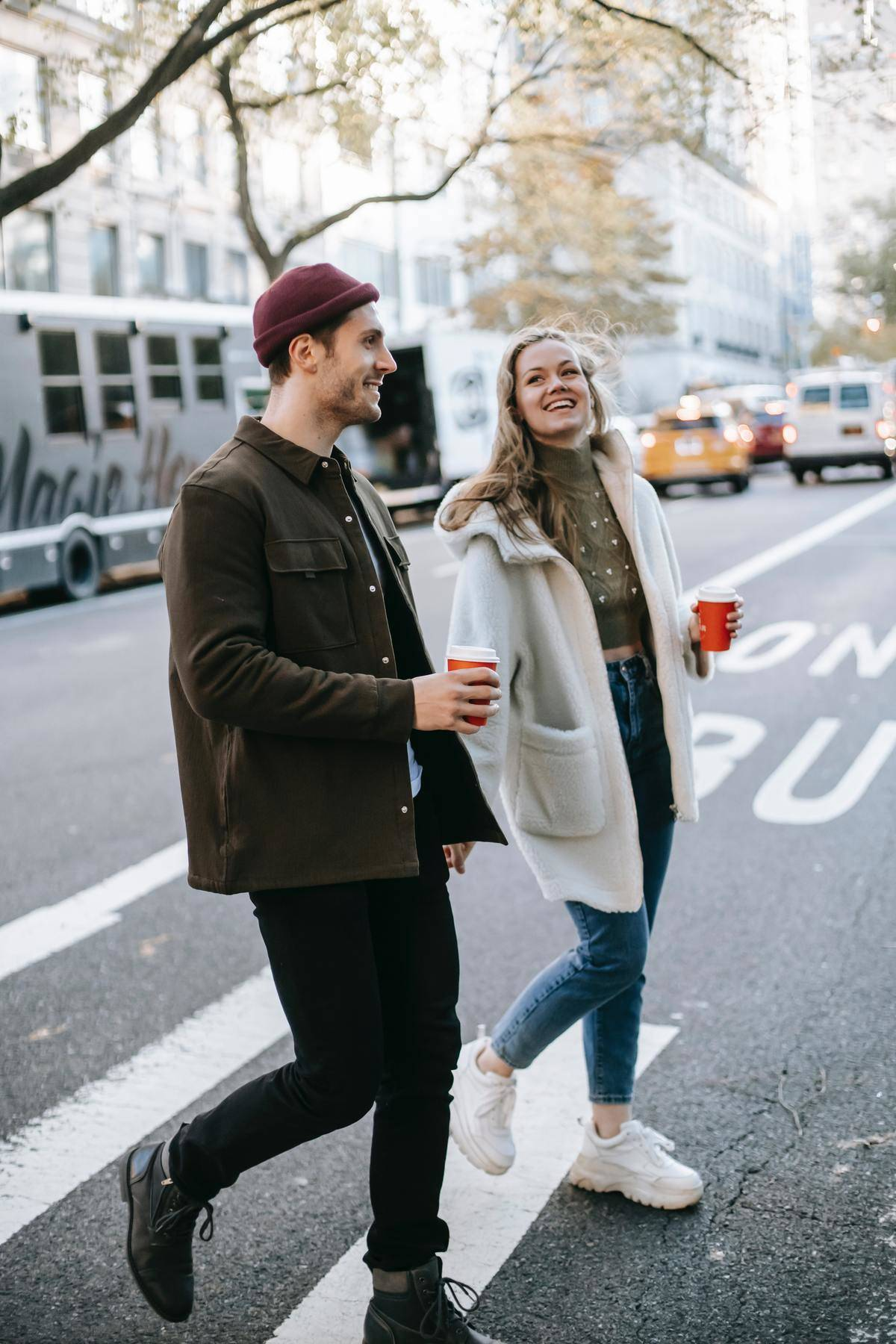 Couple crossing the road with coffees