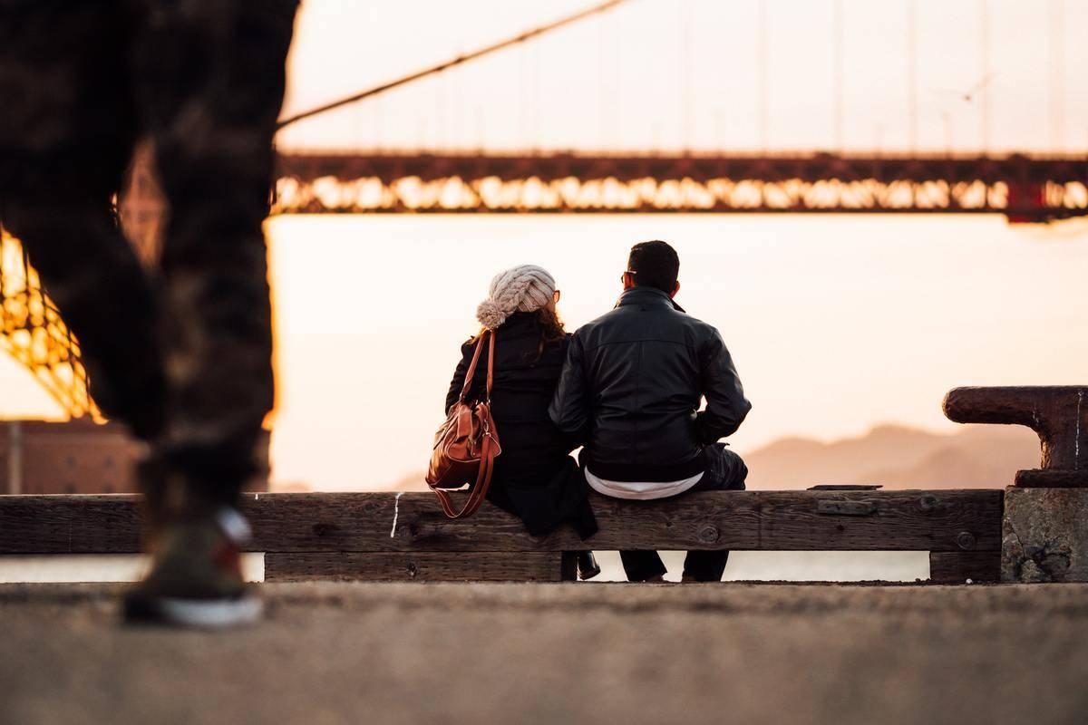 Couple sits at sunset watching Golden Gate bridge