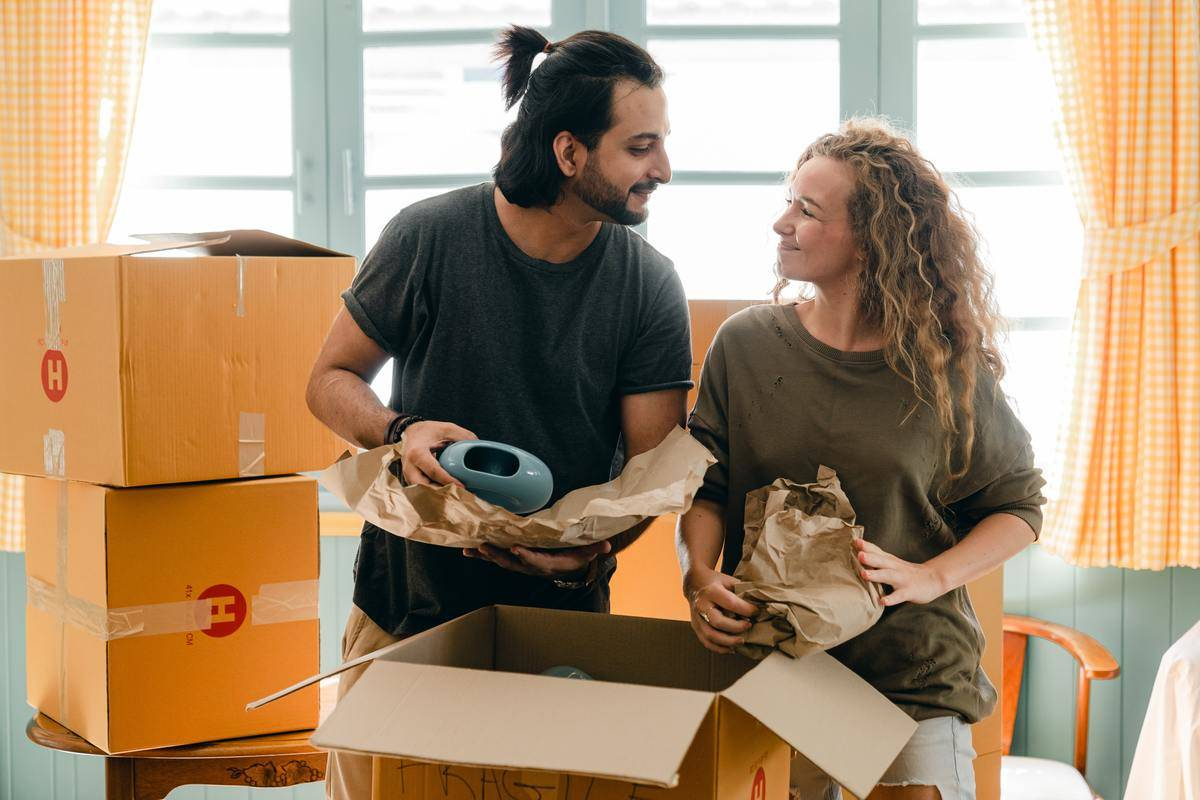 Young couple unpacks boxes moving in together