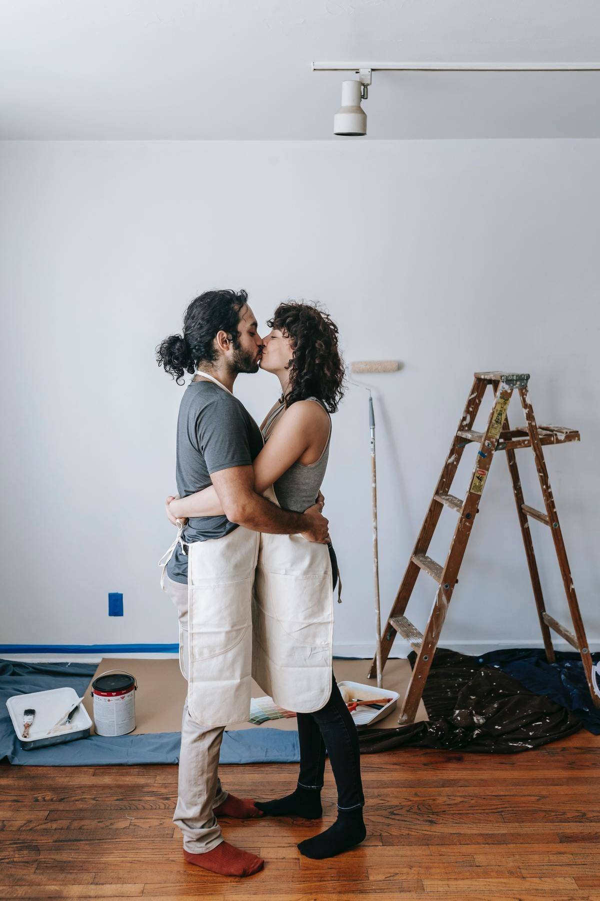 Couple takes a break from painting to kiss