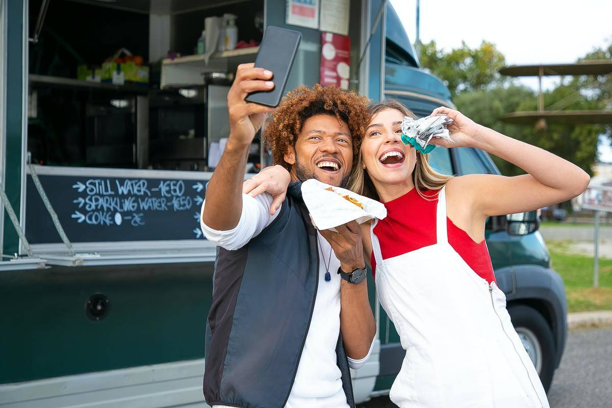 Two people taking selfie in front of food truck