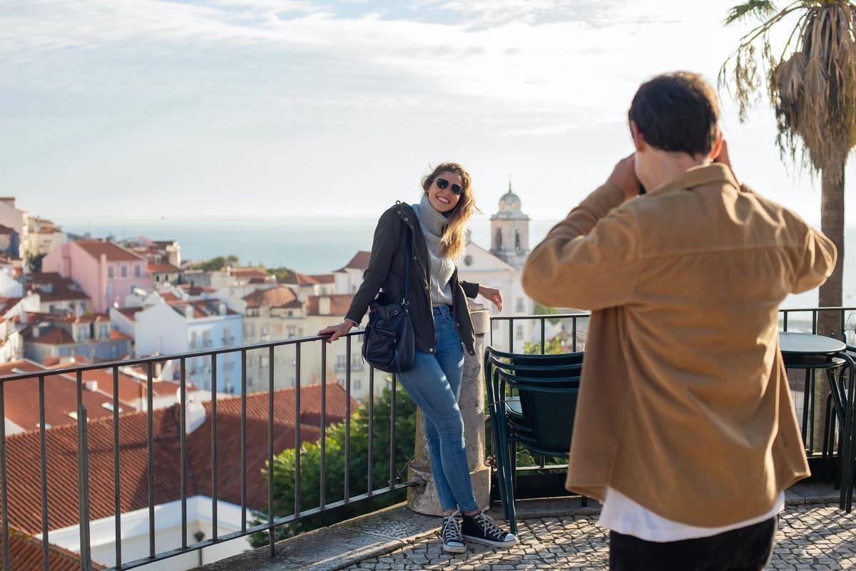 Couple traveling man snaps photo of woman posing